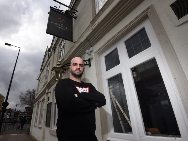 Mario Selmani outside the Whitesmiths Arms and, inset, the broken window
