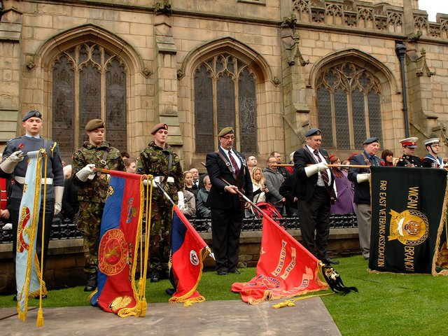 Standards are lowered during the service at Wigan Parish Church in 2010.