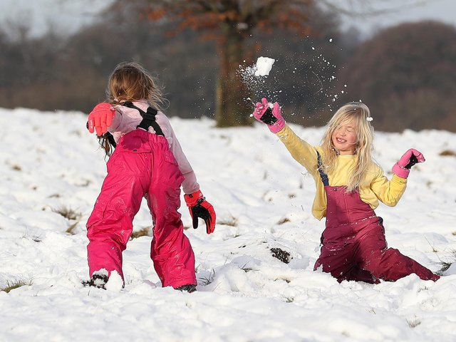 Ruby Millington (left) and Molly Chamberlain play in the snow at Tatton Park, Knutsford