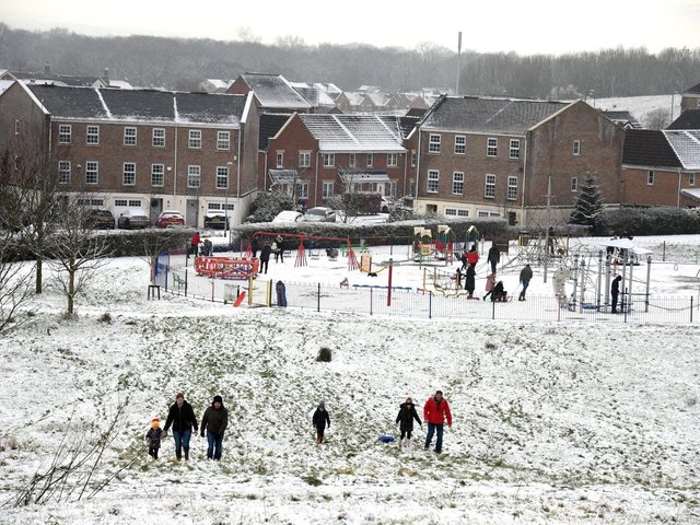 Families enjoy the snow in Buckshaw Village, near Chorley, earlier this week. North West Ambulance Service is urging people to be careful in the ice and snow after a recent spike in calls to the service