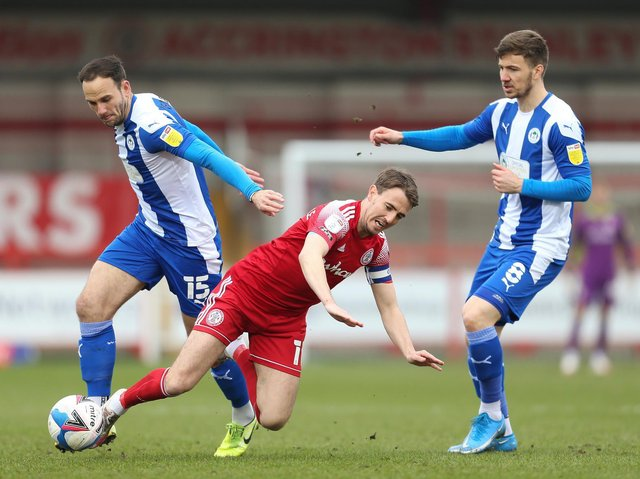 Sean McConville of Accrington Stanley is challenged by Dan Gardner of Wigan Athletic during the Sky Bet League One match between Accrington Stanley and Wigan Athletic at The Crown Ground on March 20, 2021 in Accrington, England.