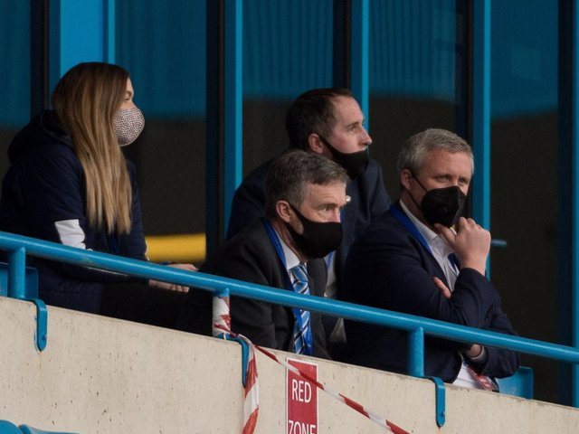 Mal Brannigan (second left) watches the recent match at Gillingham