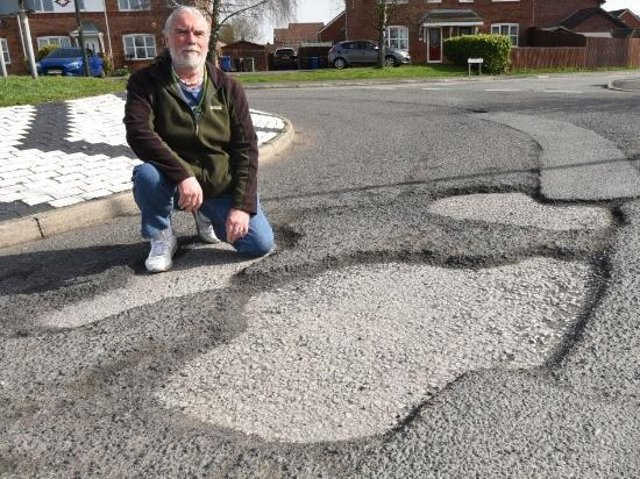 Coun John Vickers examines one of the potholes in his community