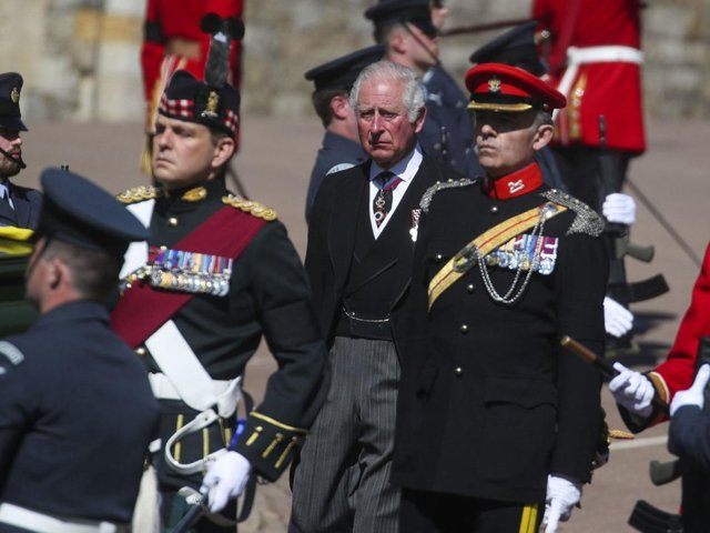 The Prince of Wales stands behind the Land Rover Defender carrying the coffin of the Duke of Edinburgh upon its arrival at the Galilee Porch of St George's Chapel, at Windsor Castle, Berkshire, during his funeral