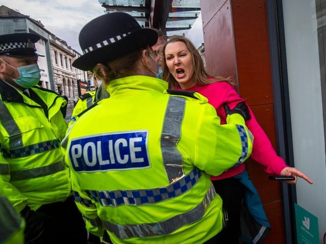 A woman without a face mask shouts and gestures towards police officers during an anti lockdown protest on November 14, 2020 in Liverpool