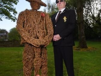 Peter Powell, treasurer of Atherton Cenotaph Memorial Project, stands next to a wicker statue