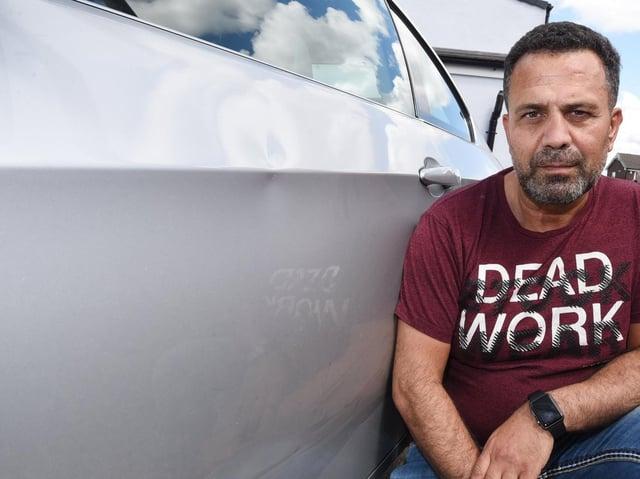 Huseyin Yalcin Kaya with his damaged car