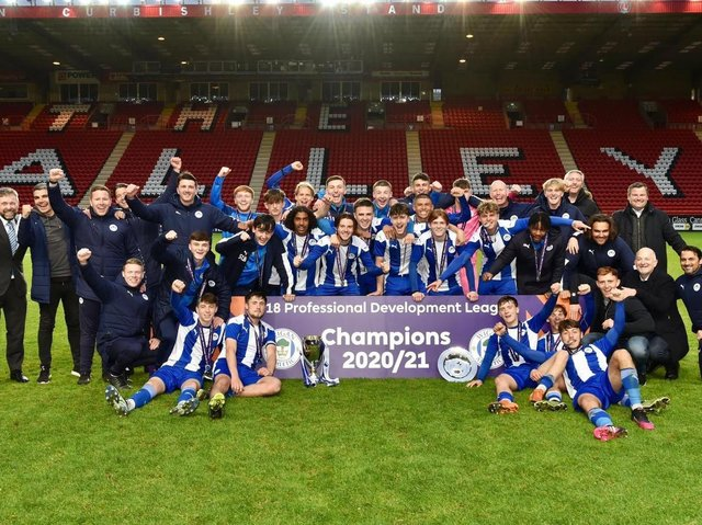 Staff and coaches join the Latics Under-18s in celebrating the national title