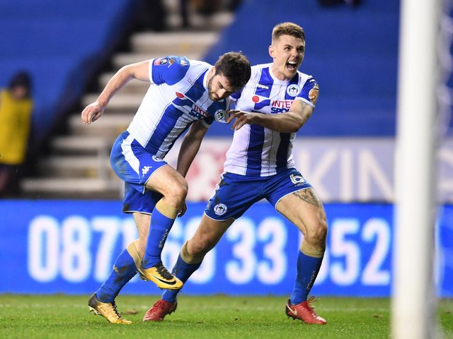 Will Grigg celebrates his winning goal against Manchester City in the FA Cup with Max Power