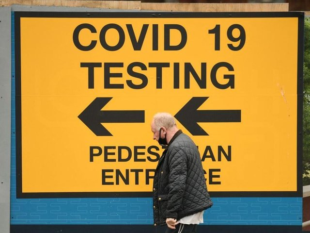A pedestrian walks past a sign directing members of the public to a Covid-19 testing centre in Bolton,