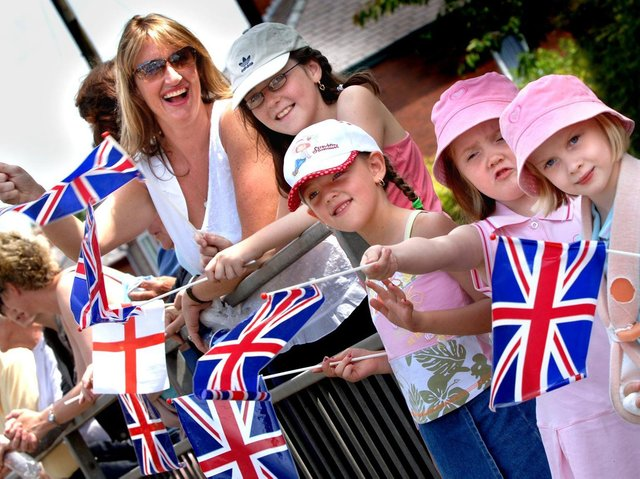 Crowds wave their flags as the VE Day parade passes in Standish, 2005.