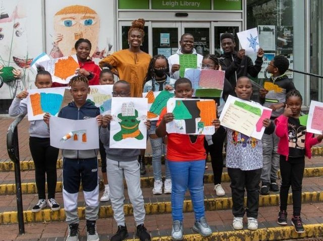 Artist Ibukun Baldwin with young people and their art for the exhibition
