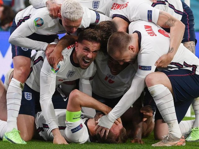 England's forward Harry Kane (bottom) celebrates with teammates after scoring a goal during the UEFA EURO 2020 semi-final football match between England and Denmark