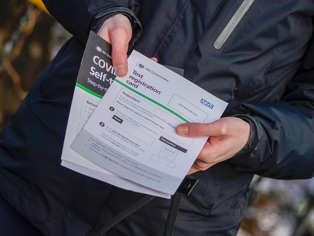 A person poses with their Test registration card after being tested at Our Lady's RC Church in Moss Side.