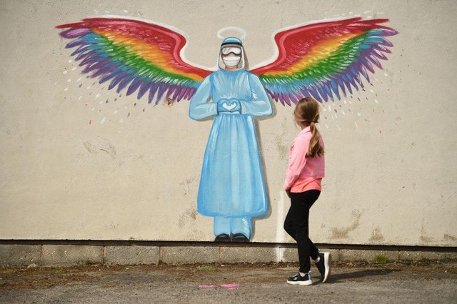 A girl looks at a mural by artist Rachel List paying tribute to NHS staff battling the COVID-19 outbreak painting on a wall in Pontefract (Photo: OLI SCARFF/AFP via Getty Images)